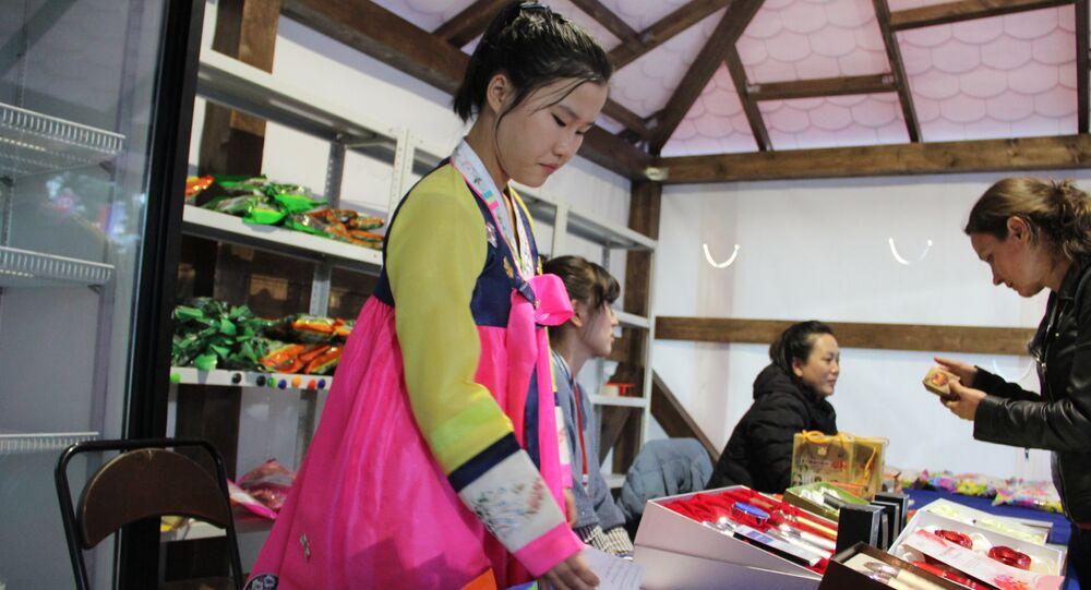 Funcionária norte-coreana, vestida de jeogori, vende produtos durante a feira em Vladivostok, em 11 de setembro de 2018