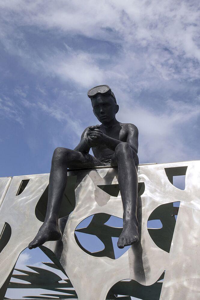Escultura de um garoto sentado sobre a galeria Coralarium, criada pelo escultor britânico Jason deCaires Taylor nas Maldivas
