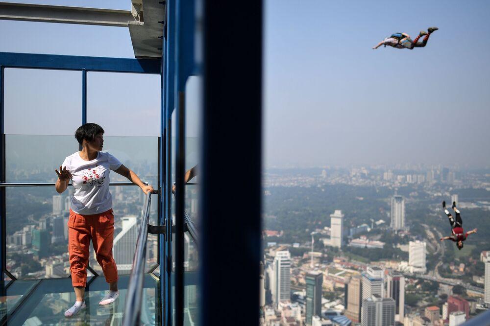 Turista observa paraquedistas pulando de um arranha-céu em Kuala Lumpur, na Malásia