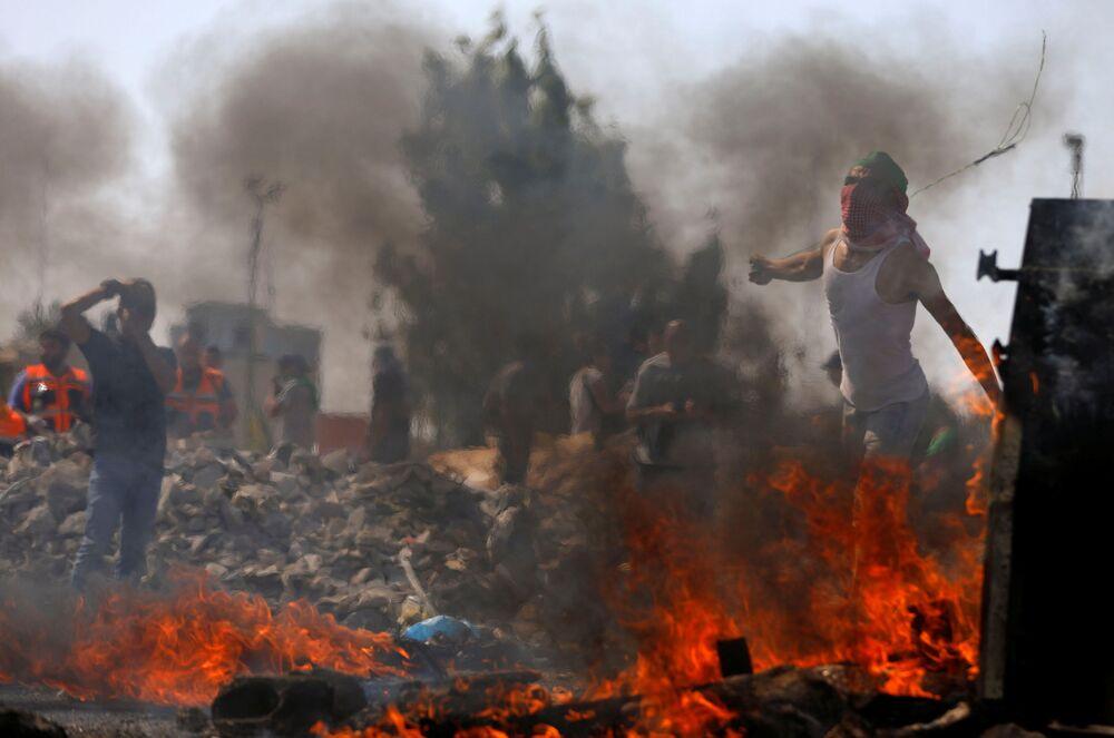 Manifestantes palestinos jogam pedras aos militares israelenses durante protestos contra os planos de eliminar a aldeia beduína de Khan al-Ahmar perto de Ramallah, na Cisjordânia