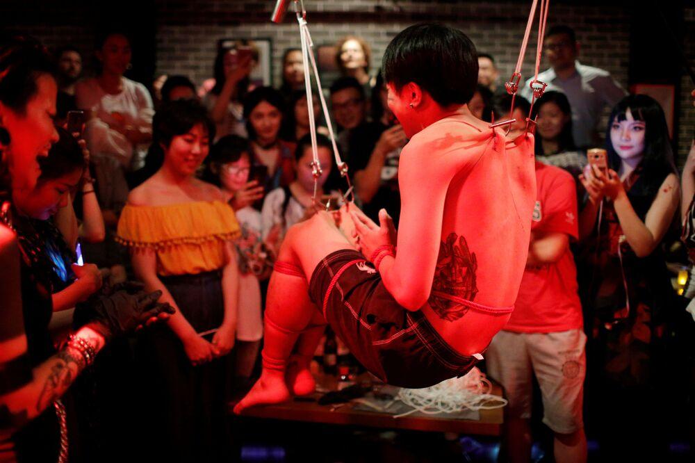 Espectadores assistem a um show de suspensão em piercings em Xangai, na China