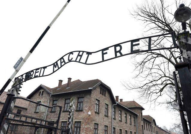 Foto da placa Arbeit macht frei (o trabalho liberta) no portão principal do antigo campo de concentração e extermínio nazista alemão Auschwitz