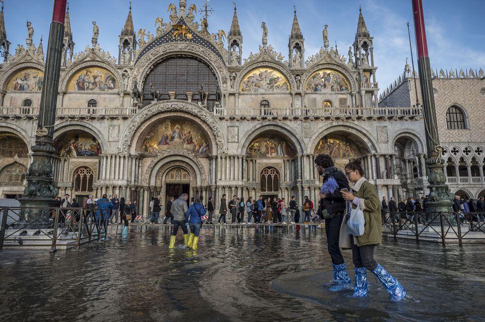 Pessoas na praça inundada de São Marcos, em Veneza (Itália), onde três quartos de seu centro histórico foram cobertos por água