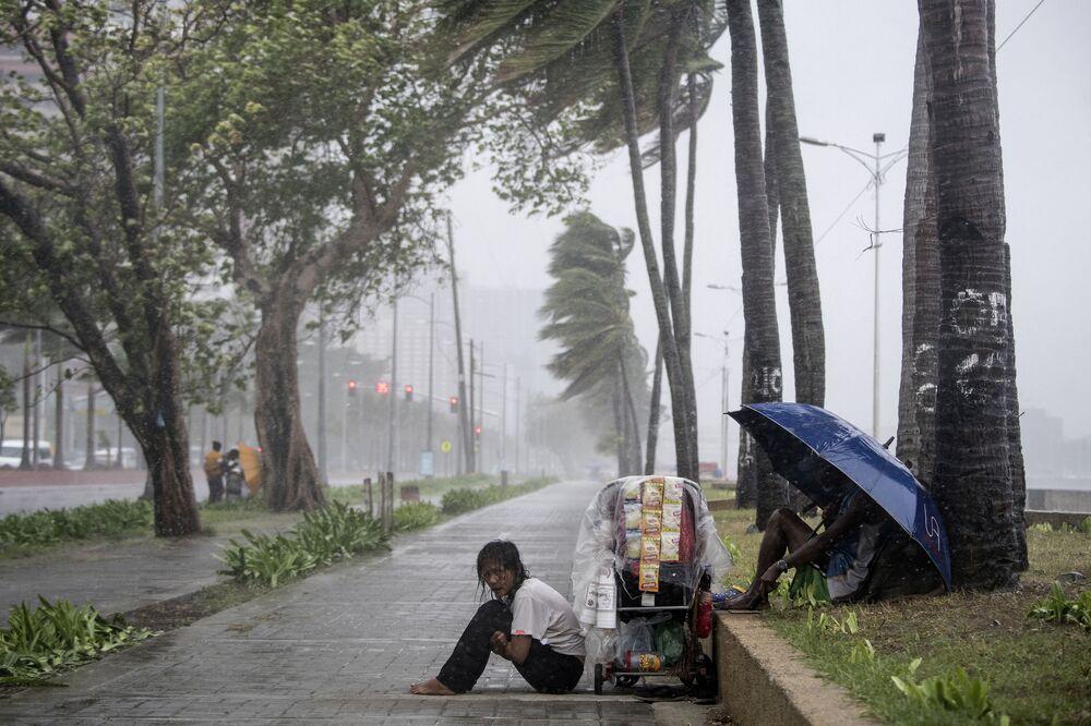 Vendedora de rua sentada no chão durante tufão Yutu nas Filipinas, em 30 de outubro de 2018