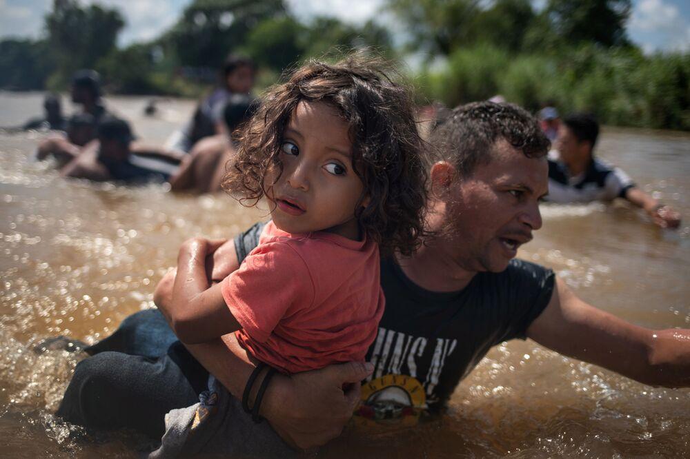 Migrantes hondurenhos dentro da água, passando pelo México e indo na direção à fronteira dos EUA em caravanas, 29 de outubro de 2018