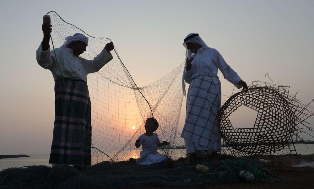 Homens ensinam artesanato à criança durante festival de Dalma Sailing, nos Emirados Árabes Unidos, em 27 de outubro de 2018