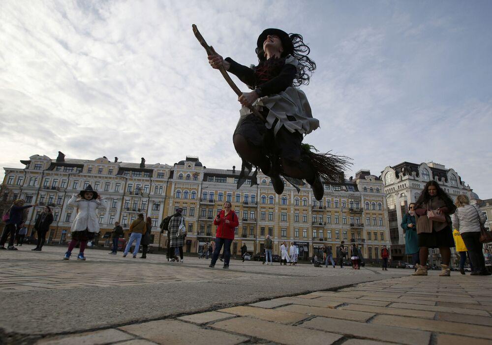 Garota fantasiada de bruxa com vassoura, durante evento Zombie Walk, no centro de Kiev, Ucrânia