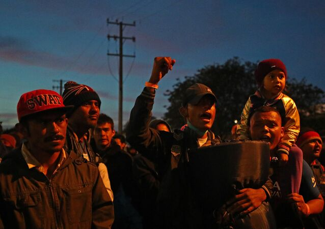 Migrants, part of a caravan of thousands from Central America trying to reach the United States, stand outside of the El Chaparral port of entry border crossing between Mexico and the United States, in Tijuana, Mexico, November 22, 2018