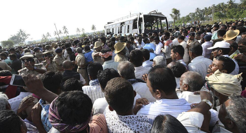 Uma multidão se aglomera em torno do ônibus recém retirado de um canal no distrito de Mandya, região sul da Índia. Ao menos 30 pessoas morreram, entre elas 5 crianças após o ônibus afundar nas águas do canal.