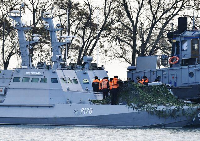 Lancha canhoneira blindada Nikopol e rebocador Yany Kapu (em fundo) da Marinha da Ucrânia detidos no porto de Kerch