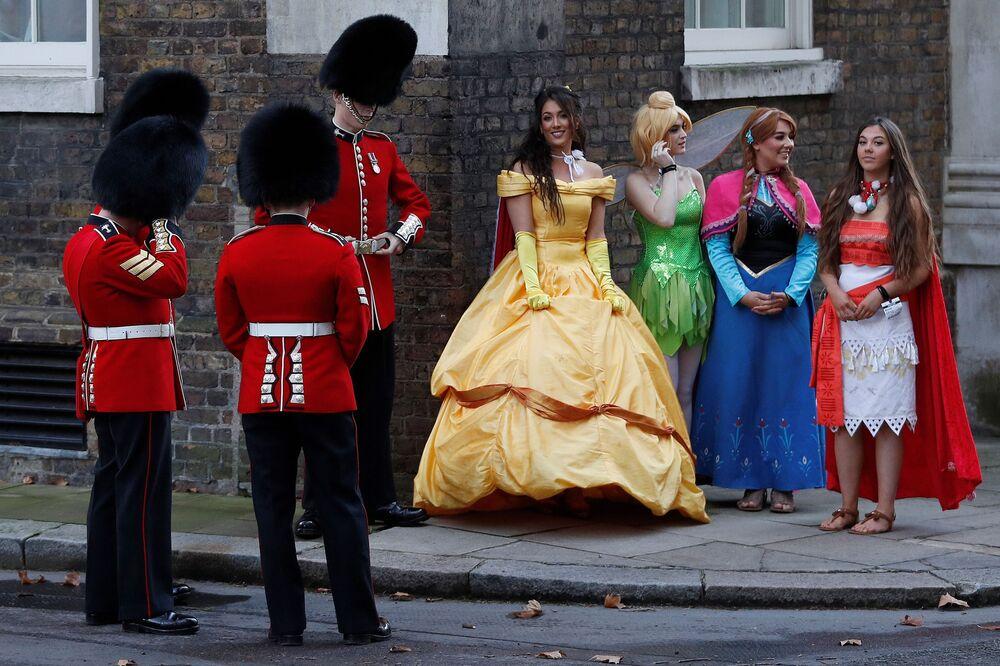 Welsh Guards, tropas de infantaria de elite do Exército britânico, ao lado de meninas fantasiadas de princesas da Disney, Londres, 17 de dezembro de 2018