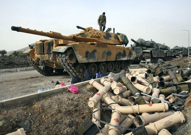 Soldados do Exército turco preparam para usar tanques nos arredores da vila de Sugedigi, na Turquia, fronteira com a Síria.