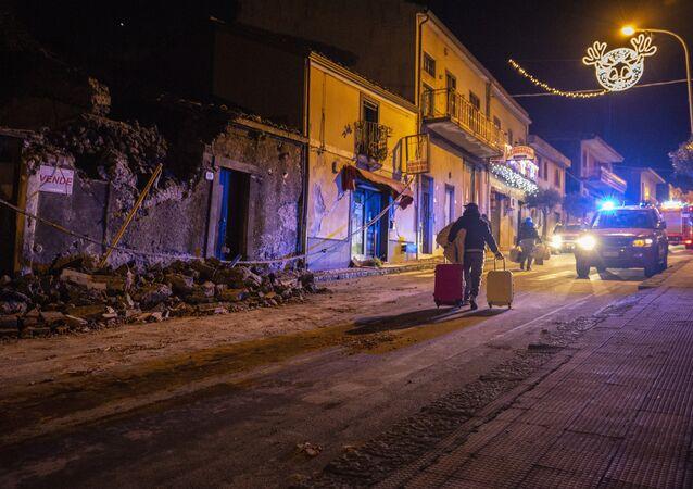 Homem carrega pertences em meio a escombros em Fleri, na Sicília, nesta quarta-feira, 26 de dezembro de 2018
