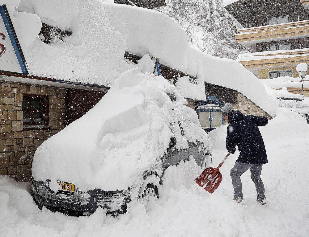 Um homem remove a neve do seu carro em Filzmoos, Áustria
