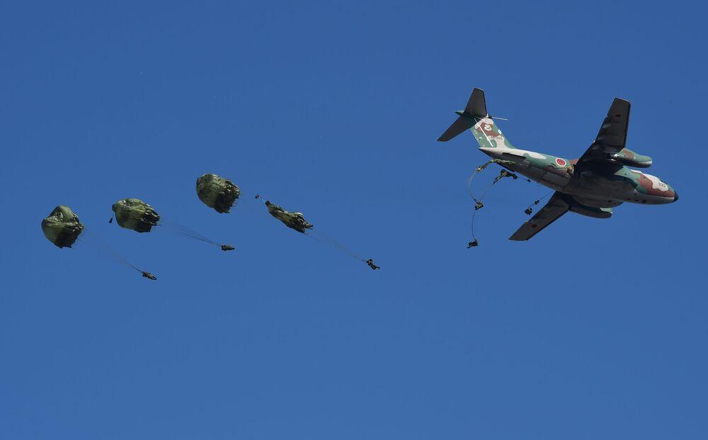 Paraquedistas da Primeira Brigada Aerotransportada japonesa saltam de um avião de transporte Kawasaki C-1