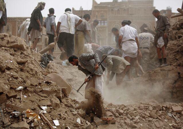 Moradores procuram por sobreviventes sob escombros de casas destruídas em ataques aéreos liderados pela Arábia Saudita no Iêmen em 12 de junho de 2015