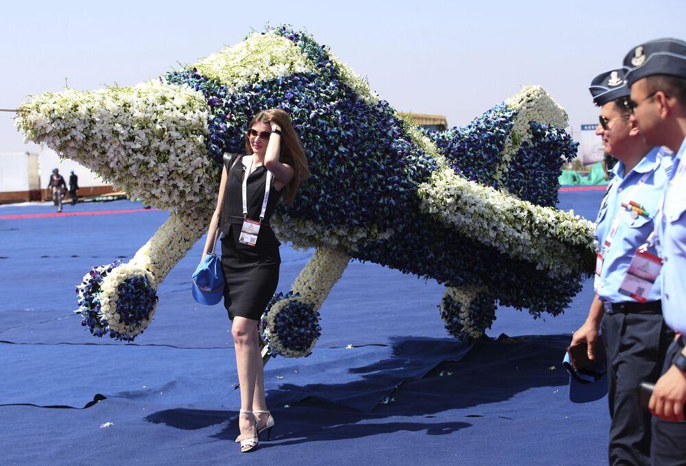 Uma visitante da exposição Aero India 2019 perto de um modelo de avião feito de flores em Bangalore, Índia