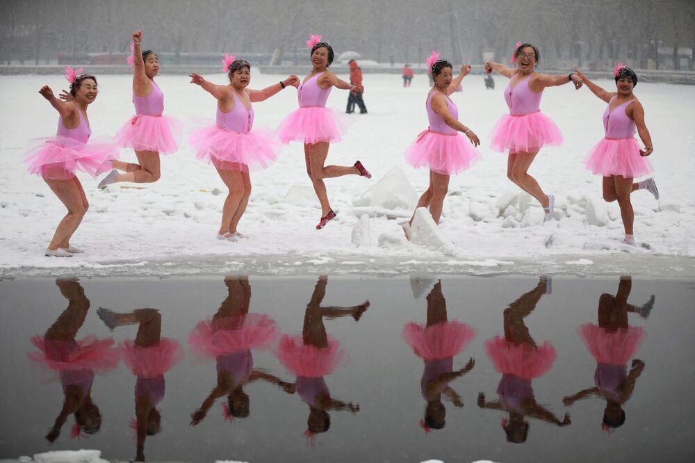 Aficionados por natação invernal vestidos em trajes de bailarina posam antes de entrar na água no parque na cidade chinesa de Shenyang