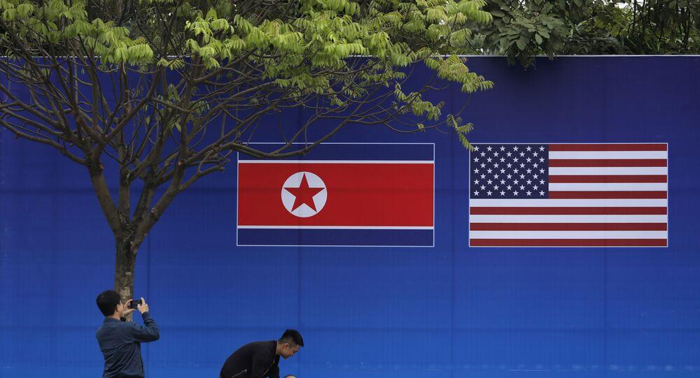 Pessoas tiram fotos em frente à bandeira da Coreia do Norte e dos EUA, em Hanói, Vietnã, 24 de fevereiro de 2019