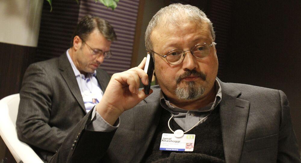 FILE - In this Jan. 29, 2011 file photo, Saudi journalist Jamal Khashoggi speaks on his cellphone at the World Economic Forum in Davos, Switzerland. Khashoggi was a Saudi insider