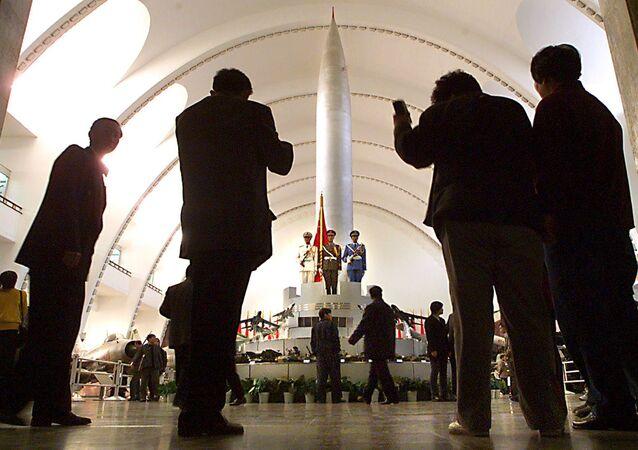 Pequineses posam para fotos em frente a um dos primeiros mísseis nucleares da China, o Dong Feng 1, em visita ao Museu Militar Que mostra as conquistas e armas militares do país.