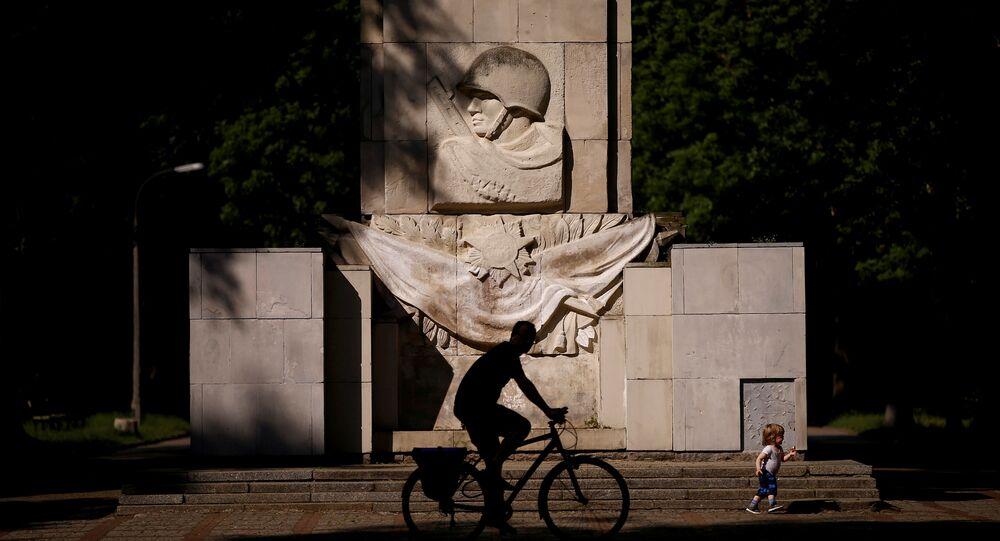 Um homem anda de bicicleta em frente ao monumento da Gratidão pelos soldados do exército soviético em Varsóvia, na Polônia.