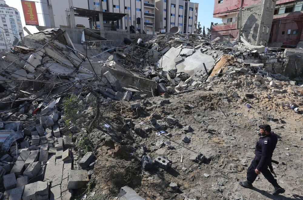 Policial do Hamas perto dos escombros de um prédio após o ataque israelense contra a cidade de Gaza