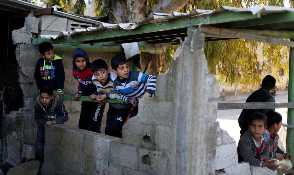 Garotos palestinos perto do prédio do Hamas depois de este ter sido alvo de um ataque aéreo de Israel