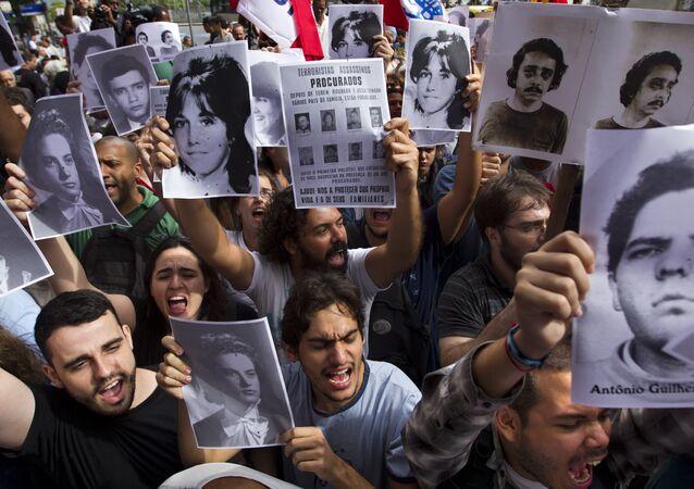 Ativistas seguram fotos de desaparecidos durante regime militar brasileiro em frente a um clube militar no Centro do Rio de Janeiro, 29 de março de 2012