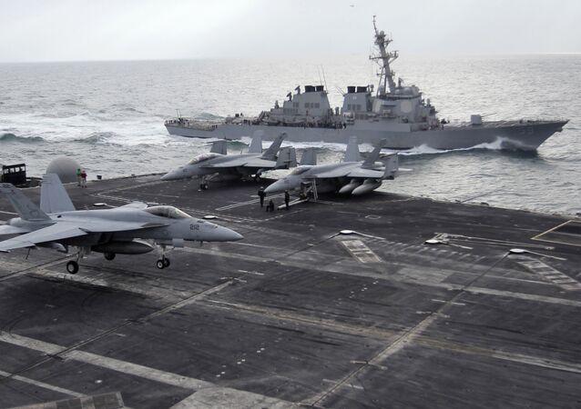 Porta-aviões norte-americano Abraham Lincoln ao lado de caças F-18 durante exercícios no golfo Pérsico