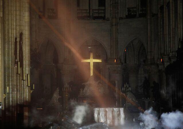 Fumaça se forma em torno do altar em frente à cruz do interior da Catedral de Notre Dame enquanto incêndio continua queimando em Paris, França, 16 de abril de 2019