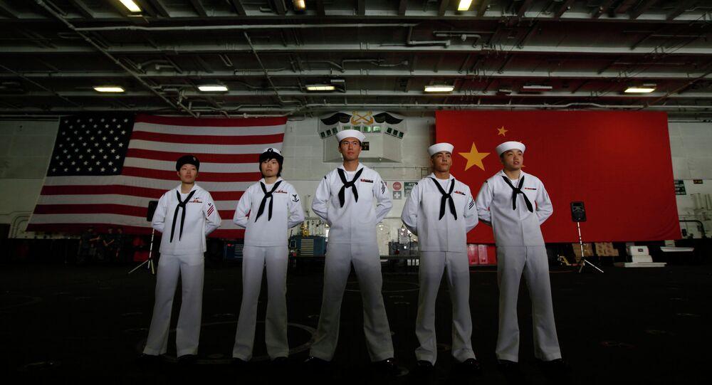 Marinheiros chineses e estadunidenses estão na frente das bandeiras da China e dos EUA