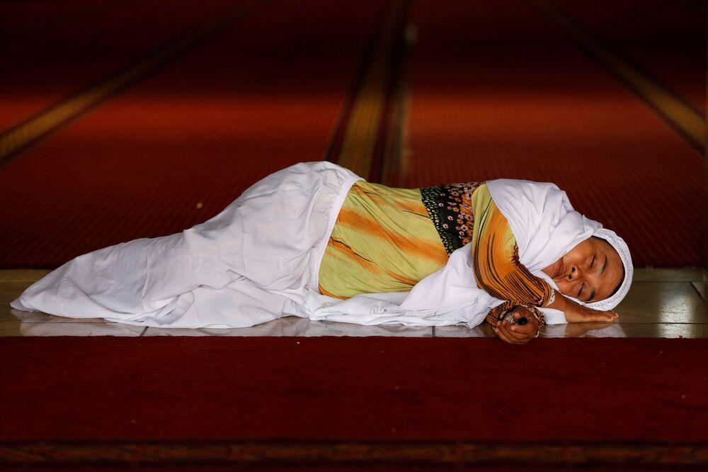 Uma muçulmana dorme enquanto espera pelo iftar (a quebra do jejum) na mesquita Istiqlal em Jacarta, Indonésia, 9 de maio de 2019.