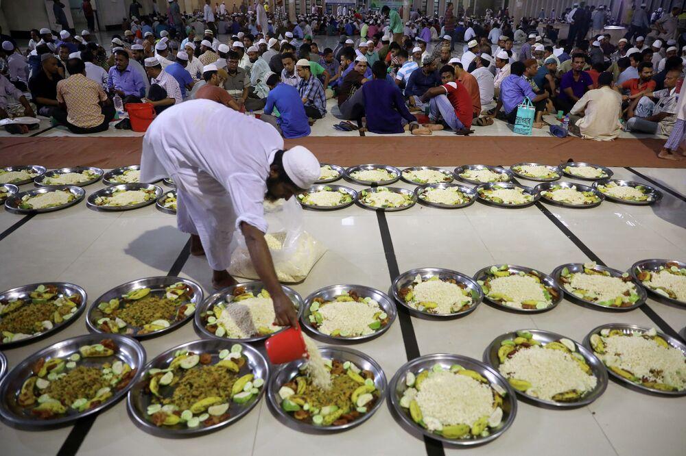 Um voluntário organiza pratos de comida na mesquita nacional de Baitul Mokarram para os muçulmanos quebrarem o jejum rapidamente durante o do Ramadã em Dhaka, Bangladesh, 8 de maio de 2019.