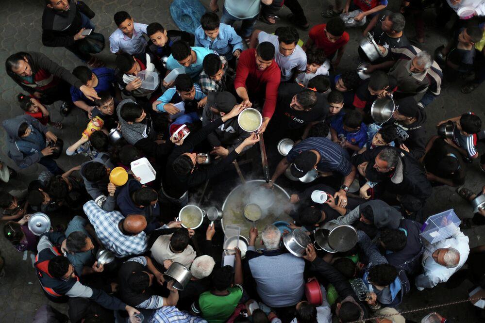 Palestinos se reúnem para receber sopa de graça durante o mês de jejum muçulmano do Ramadã, na Cidade de Gaza, 9 de maio de 2019.