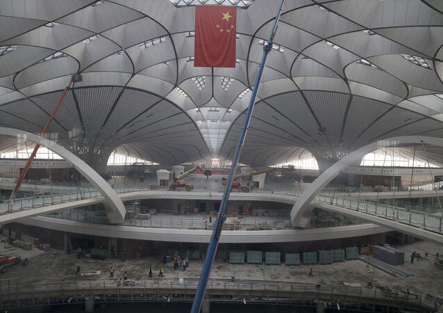 A bandeira nacional da China tremula pendurada no terminal do Aeroporto Internacional de Pequim Daxing, que está sob construção.