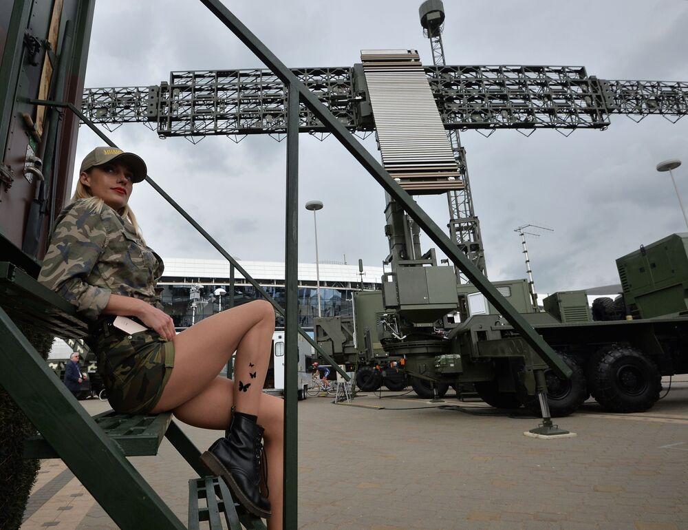 Jovem é fotografada na exposição internacional de armamento e equipamento militar MILEX 2019, em Minsk