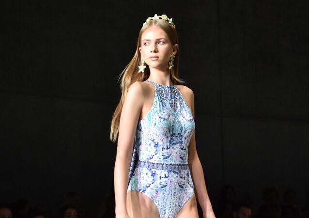 Modelo posa usando apenas um maiô delicado e uma tiara durante desfile da coleção da Aqua Blu