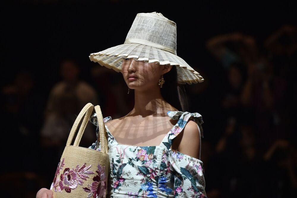 Com sombreiro e bolsa praieira, modelo desfila usando vestido com estampa de flores da nova coleção do estilista australiano Tigerlily na Austrália Fashion Week, em Sydney