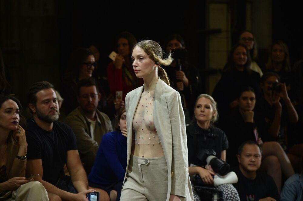 Modelo desfila usando uma blusa transparente por dentro de casaco que combina com calça da nova coleção de Karla Spetic