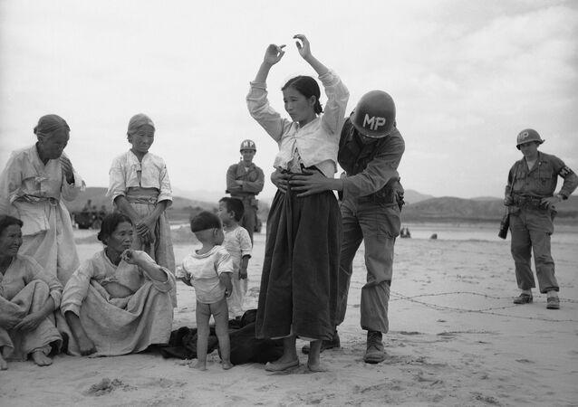 Um militar estadunidense revisa uma mulher coreana procurando armamentos escondidos (foto de arquivo)