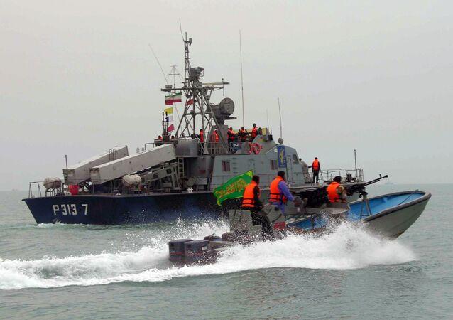 Membros da Guarda Revolucionária do Irã navegam próximo a uma embarcação iraniana durante manobras ao longo do mar do Golfo e do mar de Omã.