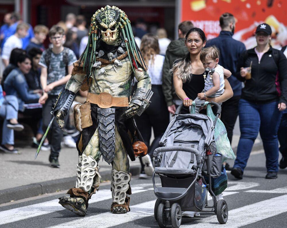 Cosplayer vestido de Predador caminha durante encontro de cosplayers na Alemanha