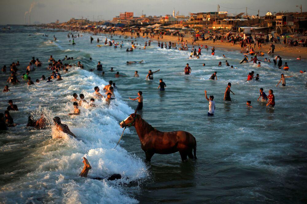 Palestino lava seu cavalo nas águas do mar Mediterrâneo enquanto pessoas nadam em dia quente no norte da Faixa de Gaza