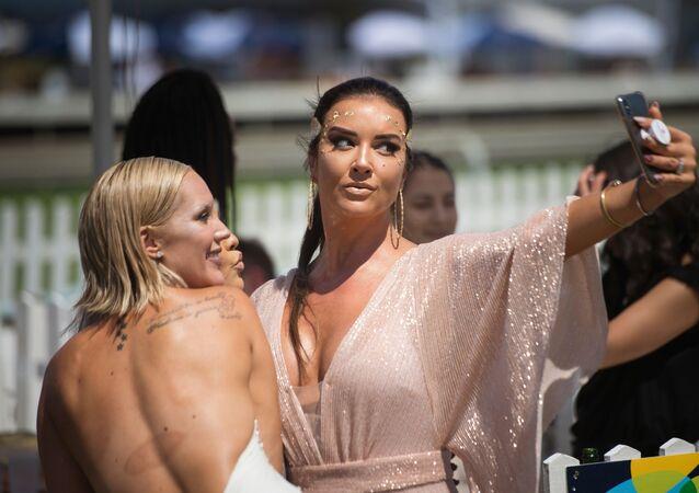 Jovens posam para selfies antes da corrida de cavalos Met na Cidade do Cabo, na África do Sul, 26 de janeiro de 2019