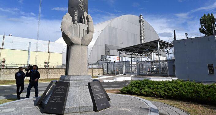Monumento perto do novo sarcófago da usina nuclear de Chernobyl, na Ucrânia, criado pela construtora francesa Novarka