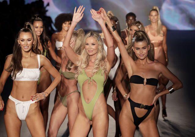 Designer de moda Monica Hansen (no centro) saúda os espectadores no show de moda de praia em Miami
