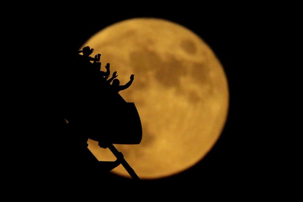 Silhuetas de pessoas em montanha russa com a Lua em fundo no parque de diversões Worlds of Fun, nos EUA