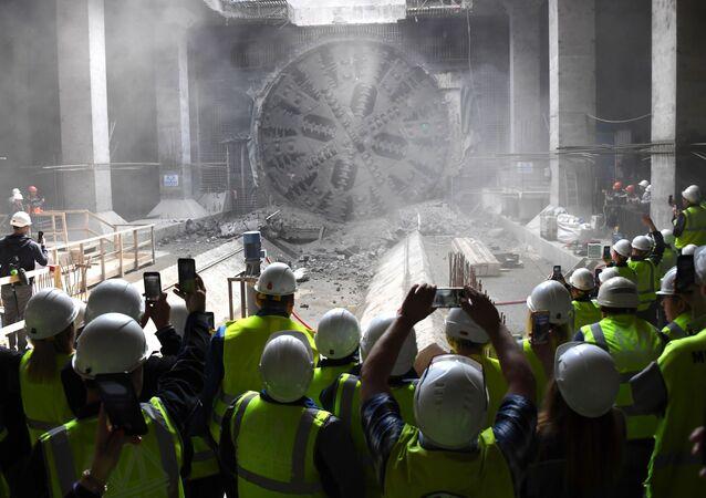 Operários tirando fotos a uma máquina de tunelamento durante a construção de uma nova estação do metrô em Moscou