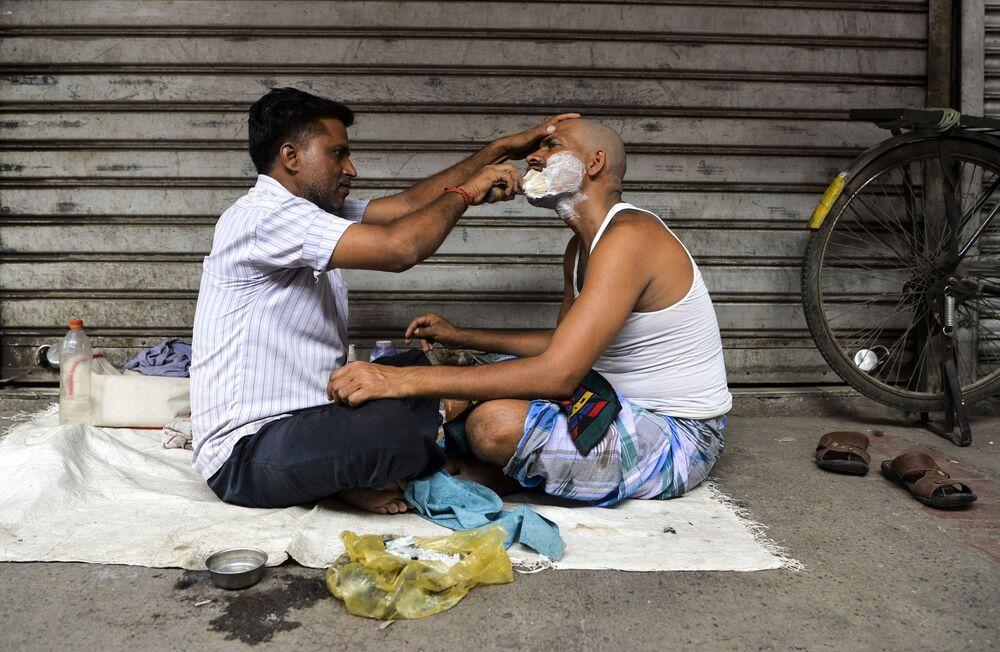 Barbeiro escanhoando o rosto de cliente no bairro velho de Nova Deli, na Índia